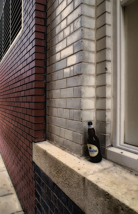 Empty Belgian beer bottle on window ledge, Liverpool, England.
