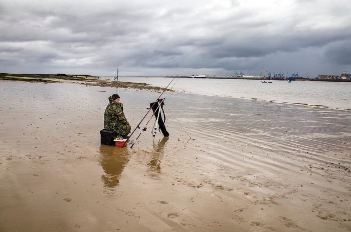 Sea angler on the beach at New Brighton, Merseyside, England.