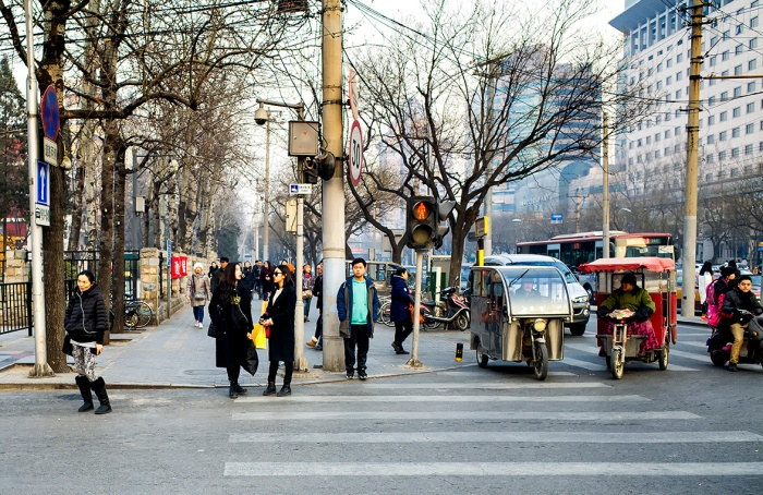 Pedestrians waiting to cross the road in Sanlitun, Beijing, China.