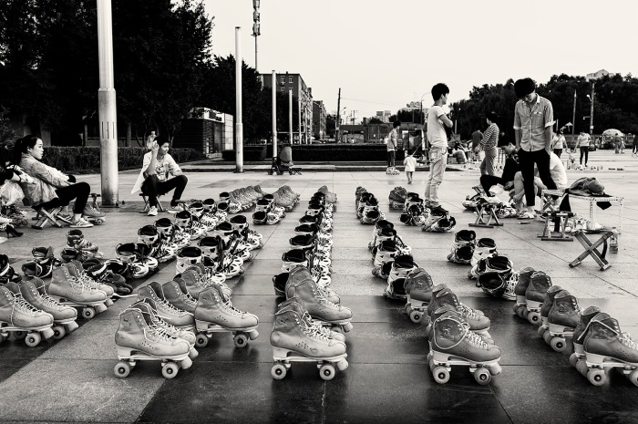 Rows of roller skates for hire on a paved area above Xizhimen Outer Street, Xicheng, Beijing, China