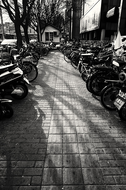 Bikes and scooters parked on the sidewalk on Fuchengmen Outer Street, Xicheng, Beijing, China.