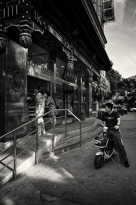 Two Chinese girls wait at the takeaway window of a restaurant on Zhanlan Road while a guy waits for them on a scooter, Zhanlan Road, Xicheng, Beijing, China