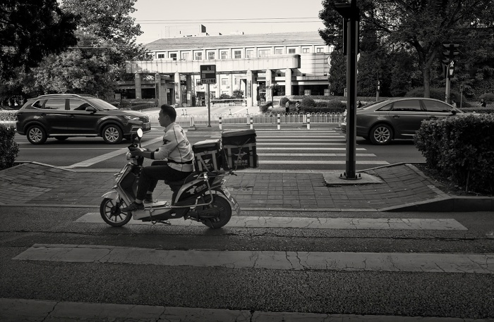 Takeaway delivery rider on the access road of Zhanlan Road, Xicheng, Beijing, China.