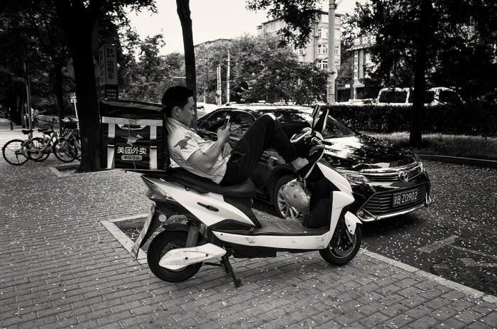 Food delivery man takes a rest on his electric scooter on the sidewalk of Zhanlan Road, Xicheng, Beijing, China.