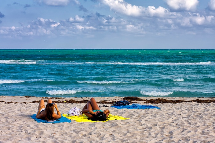 Two girls in bikinis sunbathing at Miami Beach, Florida, United States.