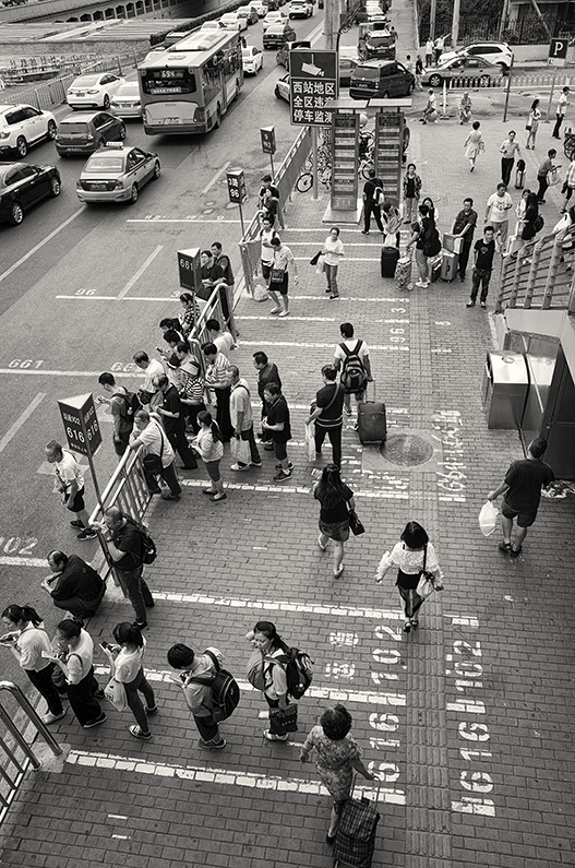 Lines of people waiting for buses on Lianhuachi E Road, Fengtai, Beijing, China.